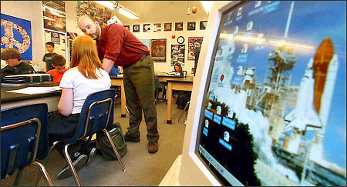 An image of a Columbia space shuttle launch serves as the screensaver on a classroom computer as teacher Alex Koerger helps a student at the Brighton School in Lynnwood.