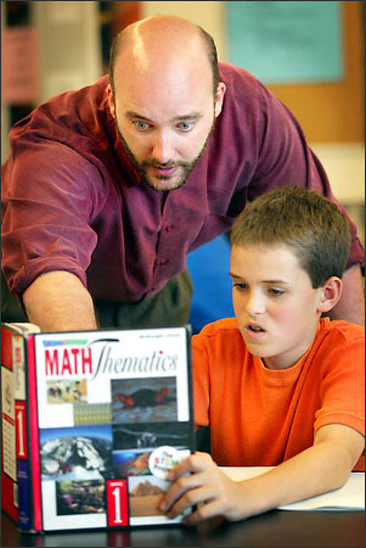 Alex Koerger, a teacher at the Brighton School, helps sixth grader Nathan King, 12, with a question during math class at the Lynnwood school. Koerger has applied to NASA for the