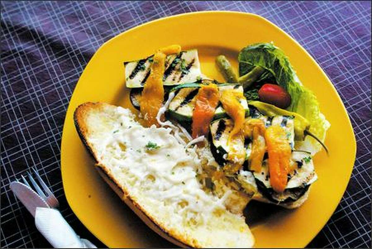 A grilled vegetable sandwich features smoky eggplant with zucchini and peppers.