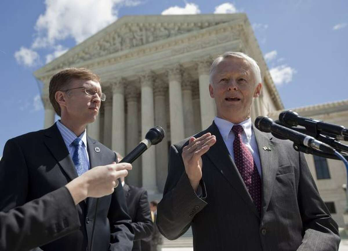Washington Attorney General Rob McKenna, left, looks on as Washington Secretary of State Sam Reed talks with media outside the Supreme Court in Washington, D.C., after justices heard arguments on whether the names on a petition asking for the repeal of Washington state's domestic partnership rights should be kept secret. (AP Photo/Evan Vucci)