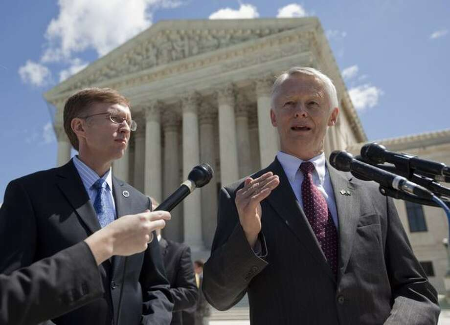 Washington Attorney General Rob McKenna, left, looks on as Washington Secretary of State Sam Reed talks with media outside the Supreme Court in Washington, D.C., after justices heard arguments on whether the names on a petition asking for the repeal of Washington state's domestic partnership rights should be kept secret. (AP Photo/Evan Vucci) Photo: Associated Press / Associated Press