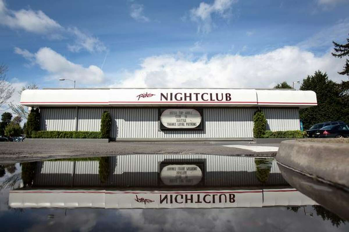 Rick's Nightclub is shown reflected in a puddle in the parking lot on Wednesday on Lake City Way Northeast in Seattle. As part of a plea deal in federal court, the notorious strip club will close.