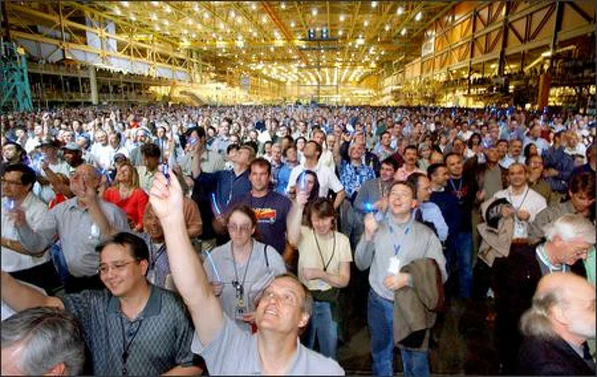 An estimated 7,000 Boeing employees in Everett raised flashlights yesterday in celebration of the sale of their new aircraft, the 7E7.