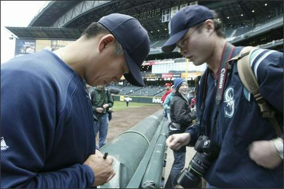 Seattle Mariners' Kenji Johjima, left, of Japan, signs an autograph for Hirotaka Sakami, also of Japan, before their game against the Kansas City Royals Sunday in Seattle. Photo: Associated Press / Associated Press