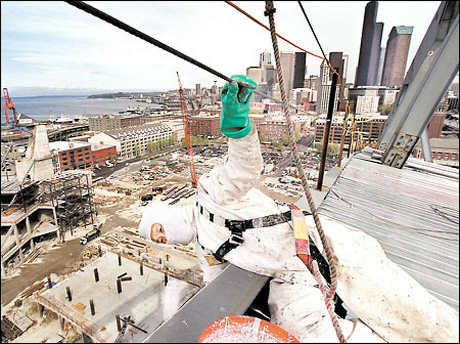 Hooked up to a harness for safety, Soo Ahn uses a roller to paint the edge of the new Seahawks stadium. From the rooftop, he has a breathtaking view of Puget Sound and the Seattle skyline. Photo: Renee C. Byer, Seattle Post-Intelligencer / Seattle Post-Intelligencer