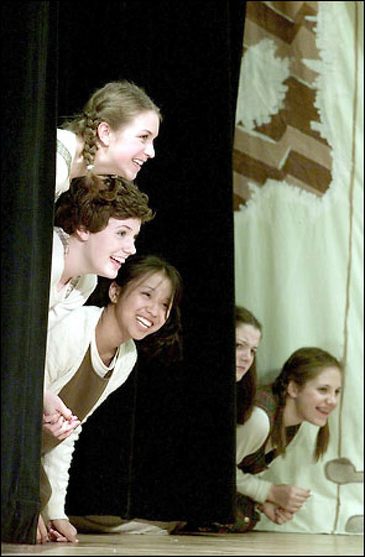 Holy Names Academy students (top to bottom) Jackie Costello, Annie Koler and Shiboo DeLeon peek out from behind the curtain in the academy's production of