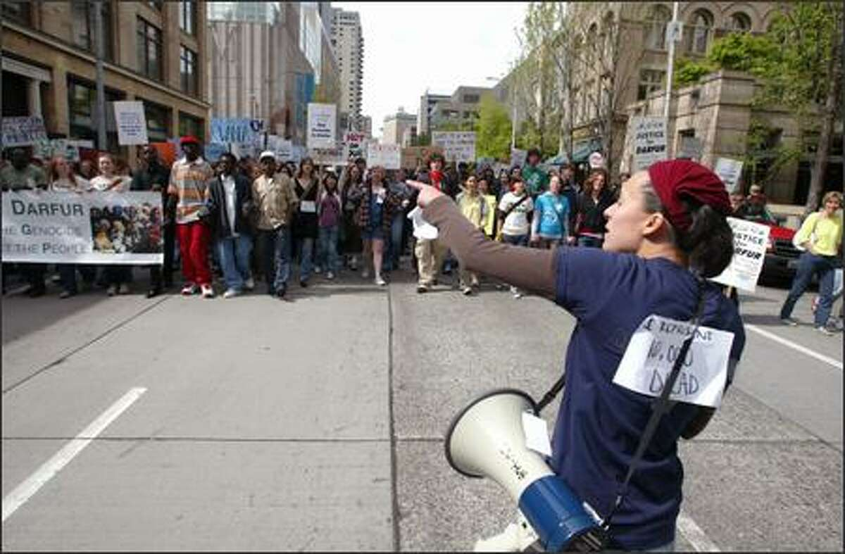 University of Washington senior Lauren Ciszak directs protesters down Second Avenue in Seattle on Sunday. UW and Lakeside School students were among those marching against genocide in Sudan.