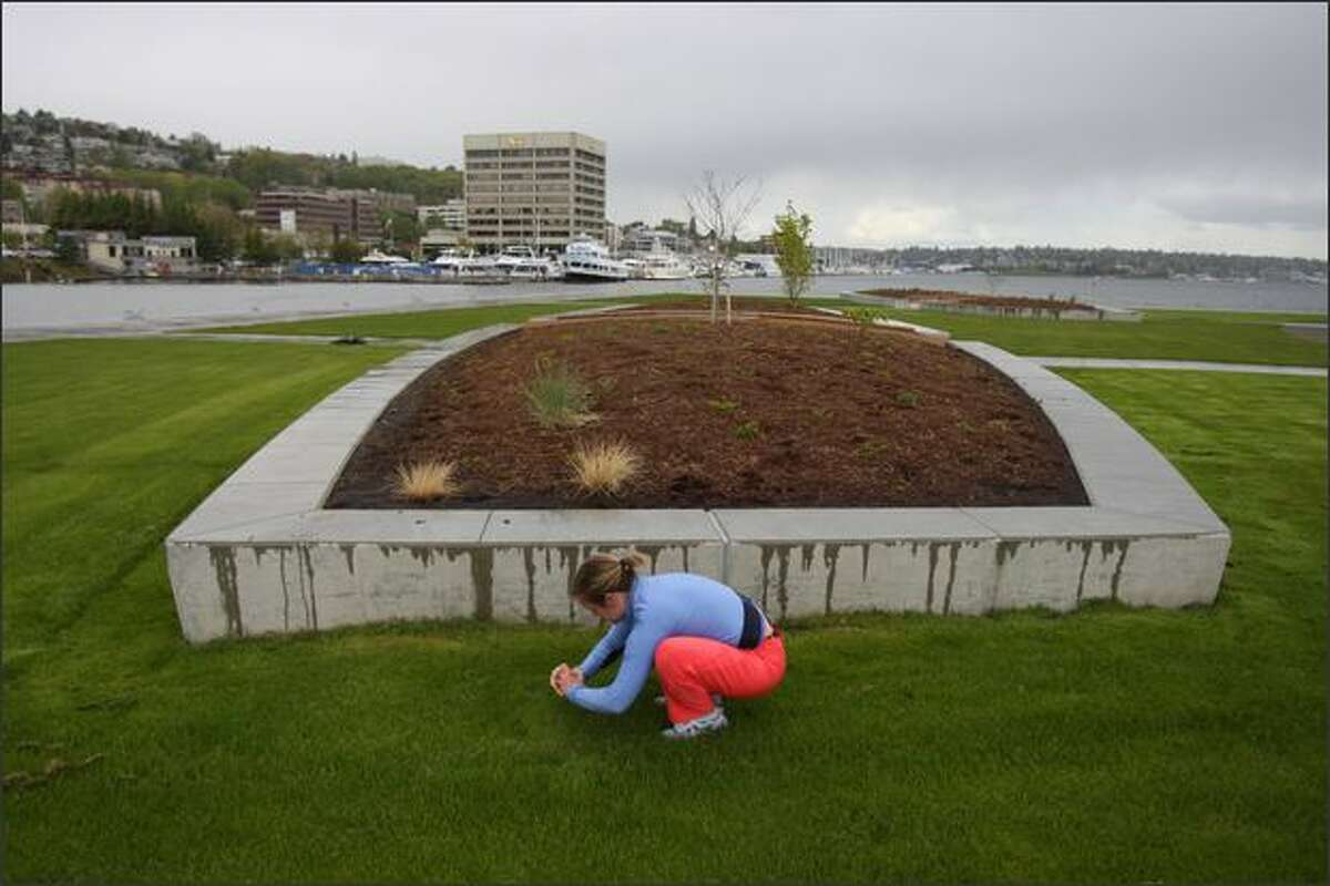 On Tuesday, Anna Leavitt stretches at Lake Union Park after running about seven miles.