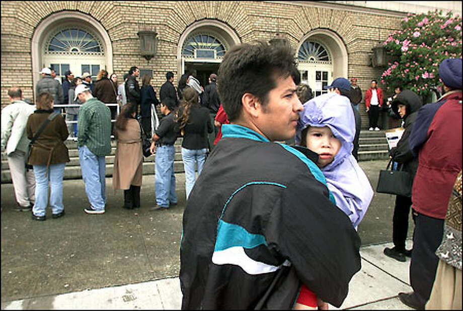 Alejandro Palacios holds his daughter Alisia, 3, as they wait outside the Immigration and Naturalization Service building in Seattle to apply for residency. Photo: Paul Kitagaki Jr., Seattle Post-Intelligencer / Seattle Post-Intelligencer