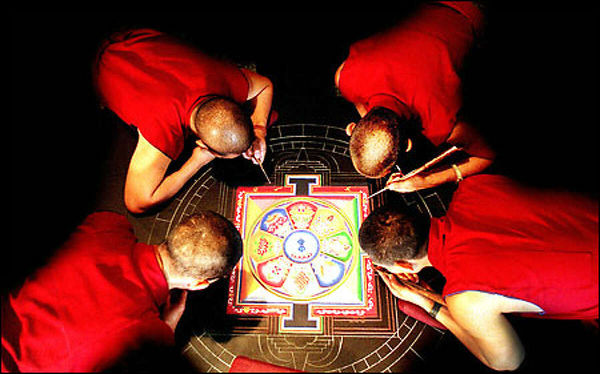 Nine Tibetan monks from Drepung Monastery in Karnataka, India, have spent the past three days constructing a sand mandala at Bastyr University at 14500 Juanita Drive N.E. in Kenmore. The monks will lead a closing ceremony, open to the public, at noon today at which the mandala will be destroyed, as a metaphor for the impermanence of life. The sands will be swept up and placed in an urn; half of the sand will be distributed to the audience, and the remainder will be carried to and deposited in a nearby body of water.