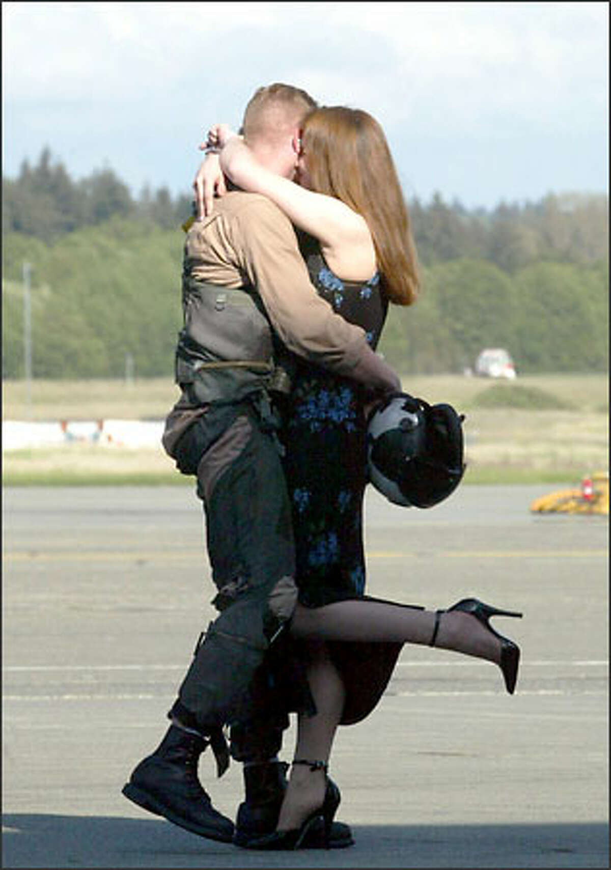 Lt. Jeff Barrett, an EA-6B Prowler pilot, embraces his wife, Kate, after arriving at Whidbey Island Naval Air Station yesterday.