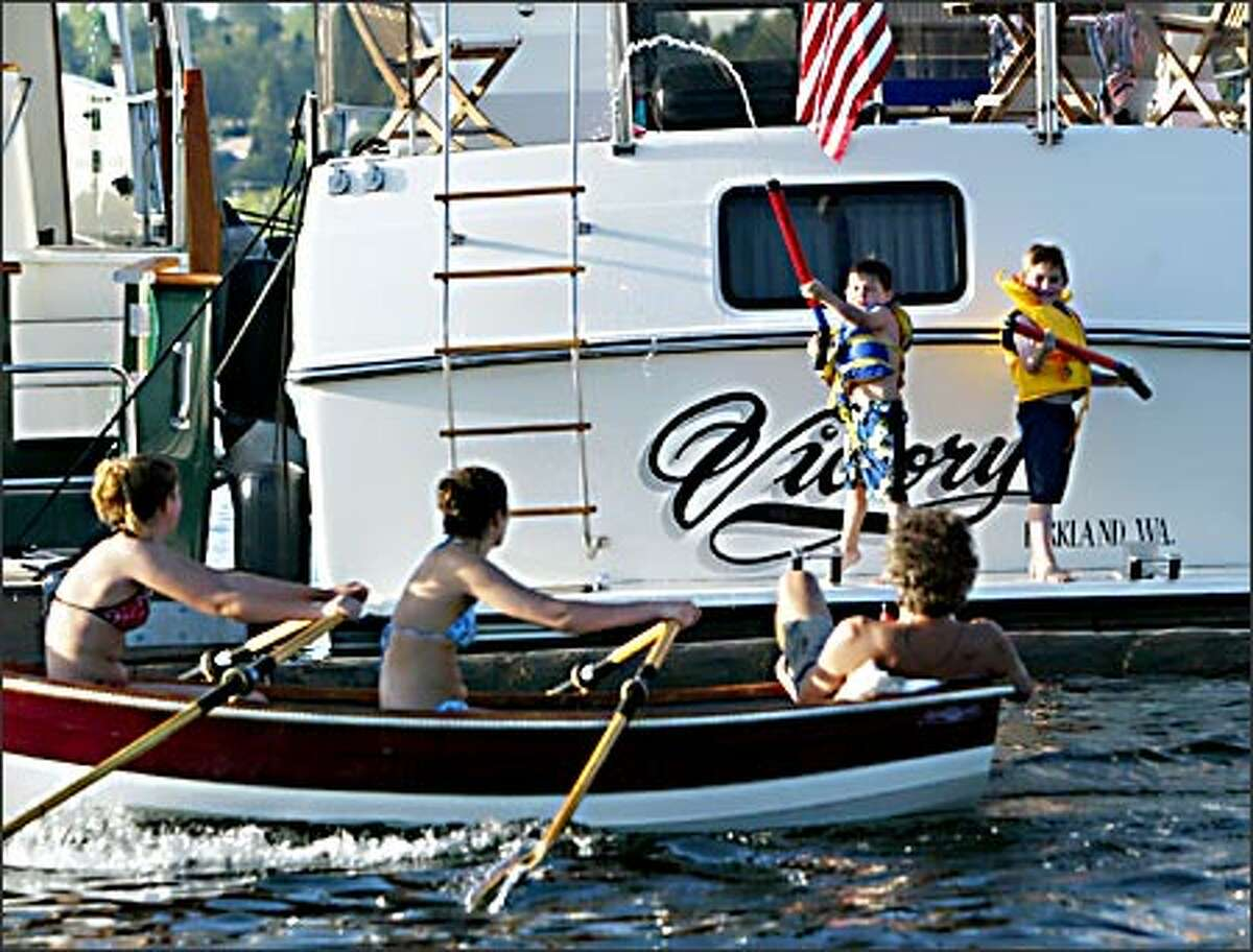 Westin Miller, 5, and Zachary Dinger, 6, wield water blasters as, from left, Alex Eravec, Margaret Ortblad and Mik Erjavec row past them on Lake Washington Friday. Boating season officially opens Saturday.