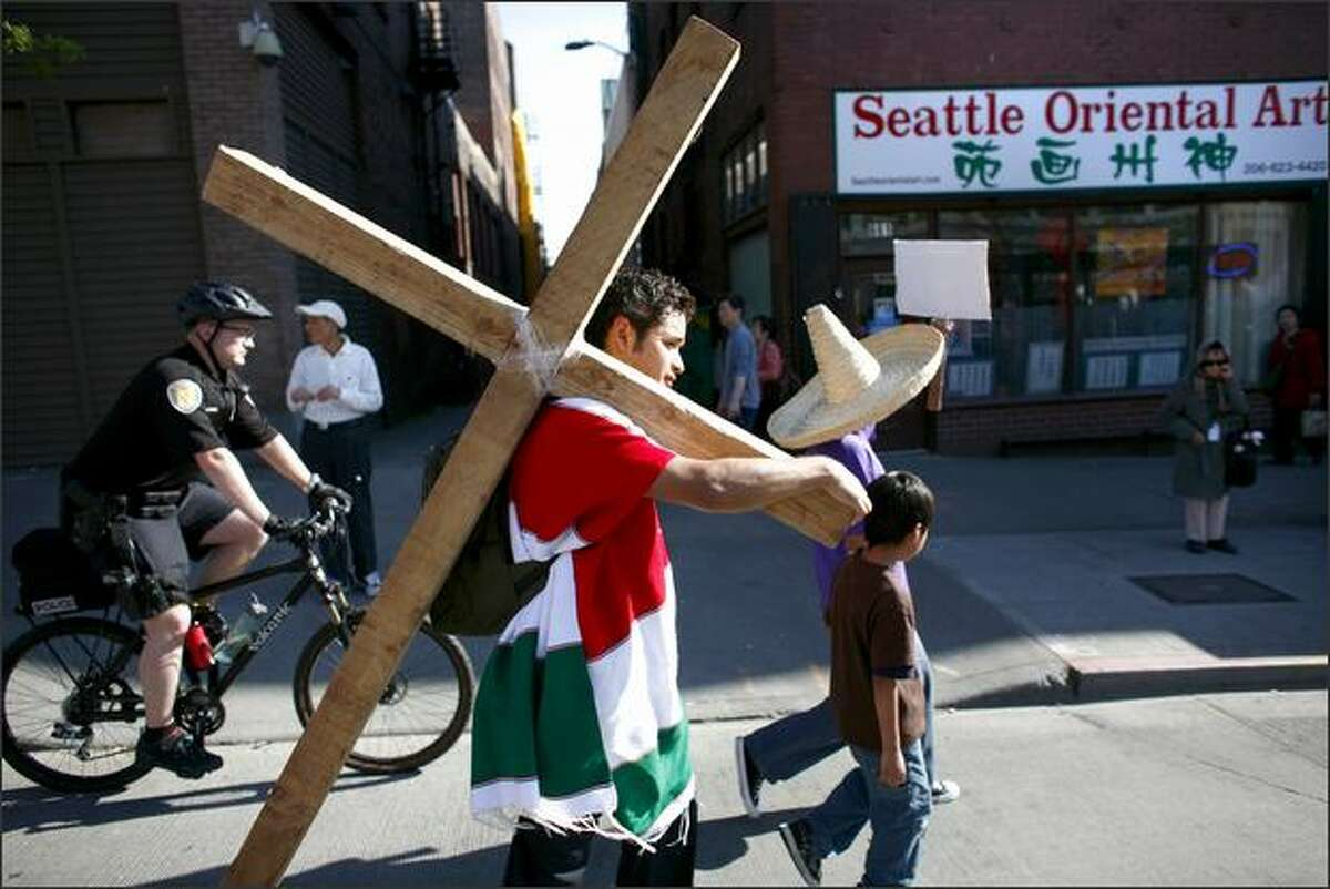 Pablo, from Mexico, carries a cross during the annual May Day march in downtown Seattle on Friday. Marchers called for immigration reform and worker rights.