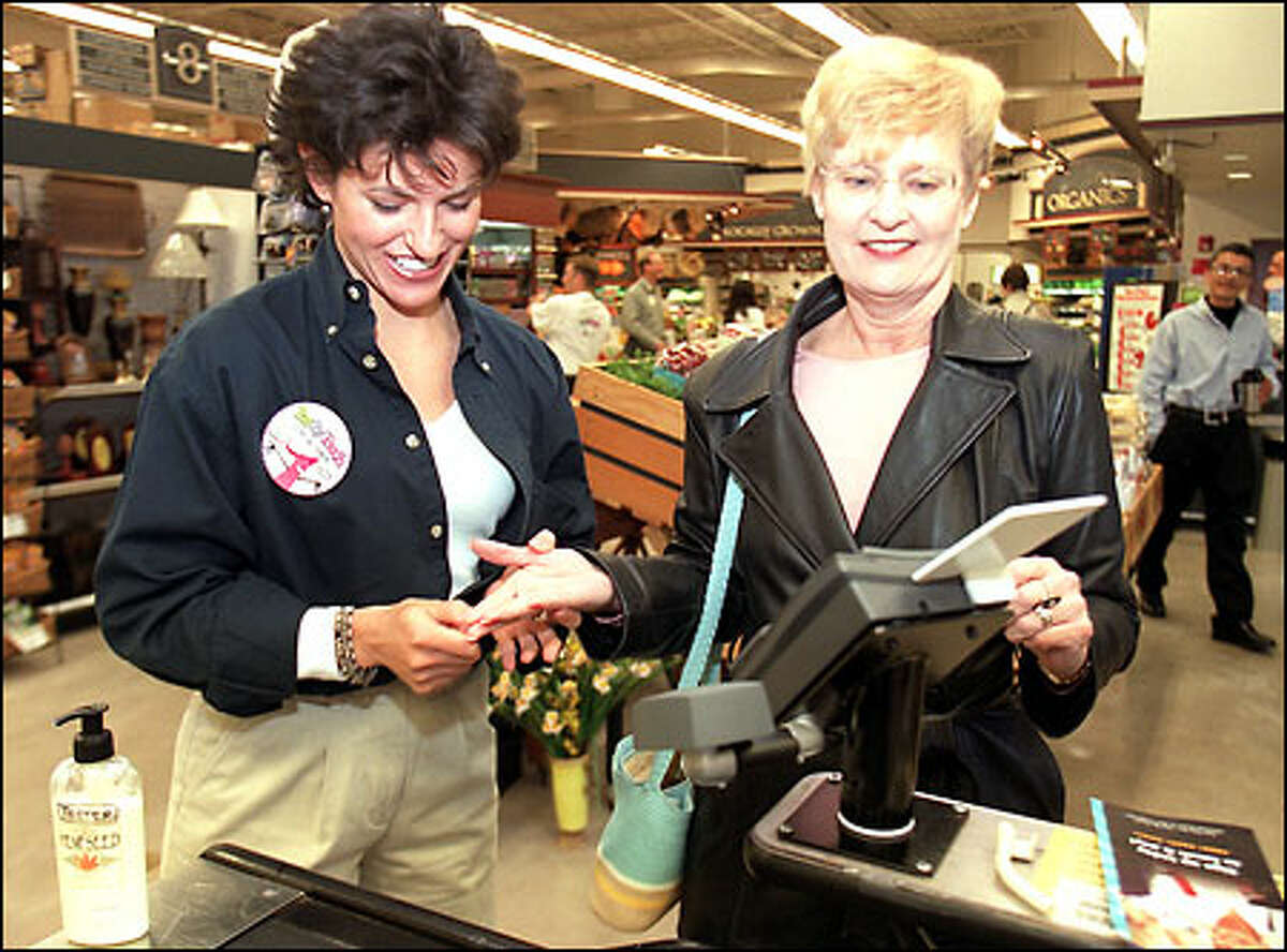 Margaret McGuire of Indivos Corp., left, helps Coleen Thompson use the new pay-by-touch system at West Seattle Thriftway yesterday.
