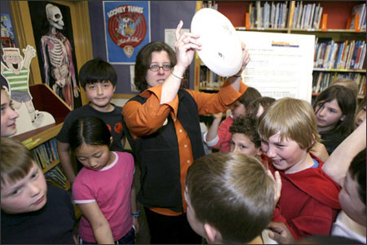 Paula Selzer, director of the SunWise initiatives for the EPA, shows students a sun-sensitive Frisbee with a blob of sunscreen on it that she will use to show the fourth-graders the power of sunscreen.