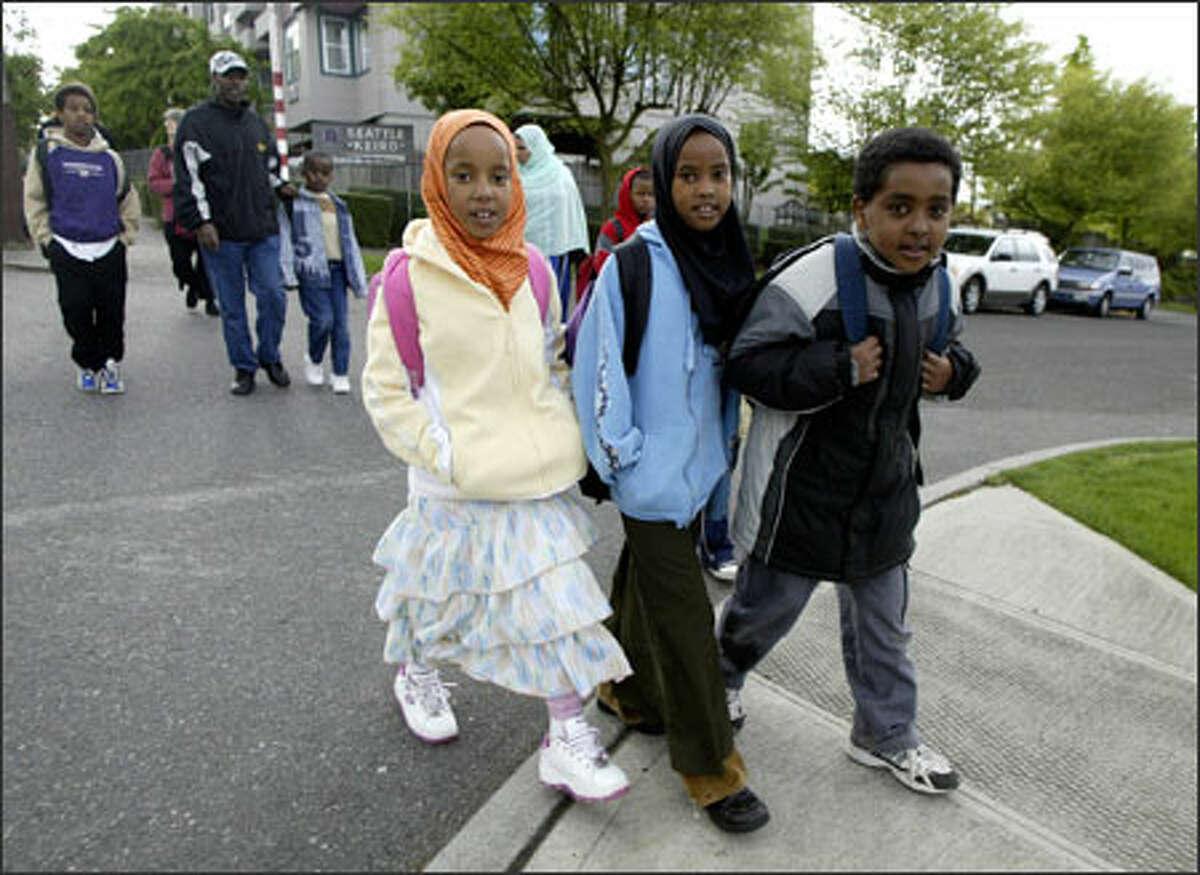 From left, Gabbiftu Aliye, 7, Asanti Umar, 8, and Tumuuda Tamaami, 8, walk to Bailey Gatzert Elementary on Monday under the
