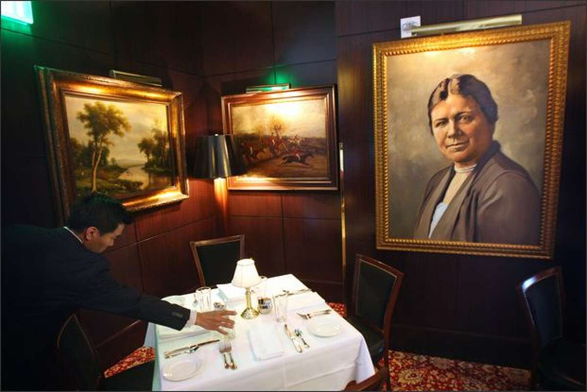 A portrait of Bertha Knight Landes, one of Seattle's early mayors, watches over a table being set by Joel Labrador, manager of the Grille. The restaurant is replete with portraits of Seattle greats and legends amid other large paintings. The dining area of this high-end restaurant is large, darkly colored, with rich textures and comfortable seating.