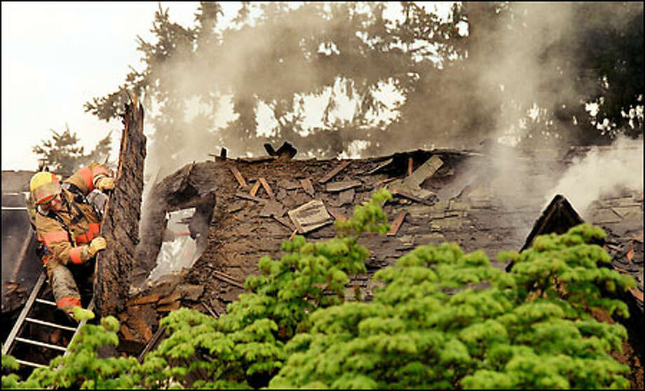 A firefighter breaks off part of the roof of a West Seattle house destroyed by fire yesterday. Janet Bundy, a 67-year-old grandmother, died from injuries from the blaze. Photo: Renee C. Byer, Seattle Post-Intelligencer / Seattle Post-Intelligencer