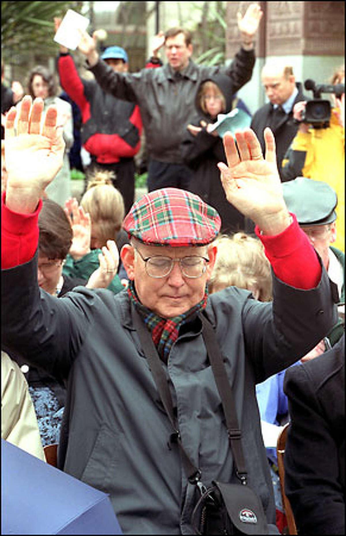 Loren Nelson, left, raises his hands in prayer yesterday in Westlake Park.