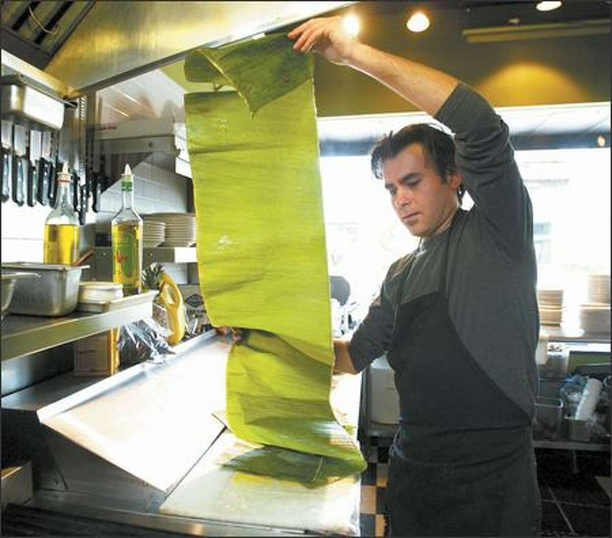 Alvaro Candela unrolls banana leaf to roast pork for tacos in a Mexican meal made for friends after hours at the Greek restaurant where he works.