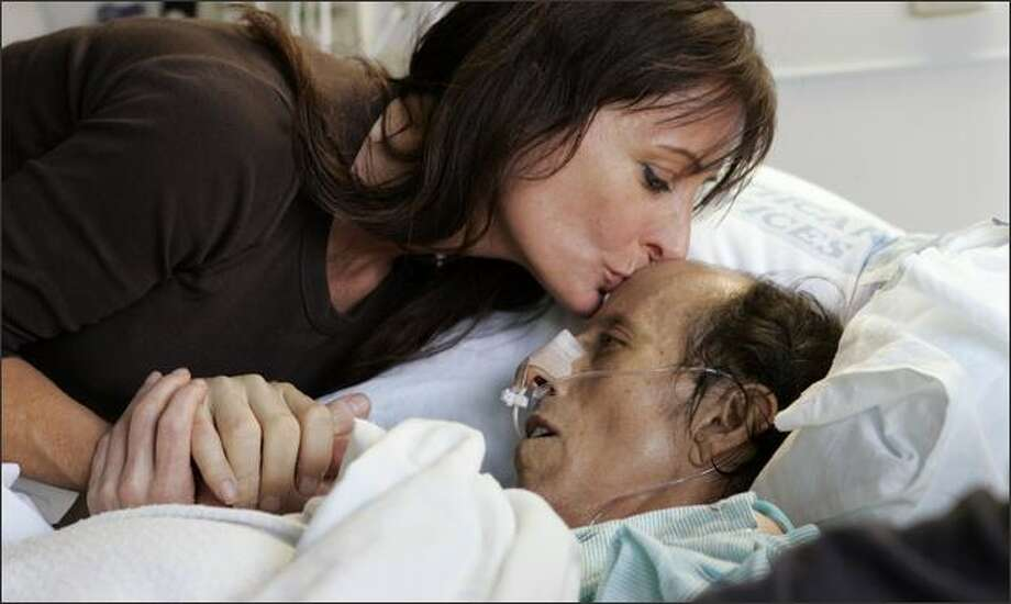 Tim Garon lay in his hospital bed as his girlfriend, Leisa Bueno, leaned over to give him a kiss while they waited April 24 to hear if he would be put on a transplant list to receive a new liver. One week after he was refused a transplant for the third time, Garon died. Photo: Associated Press / Associated Press