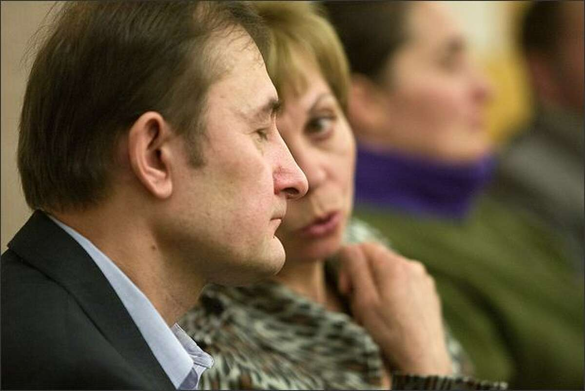In a Tacoma courtroom Friday, Mikhail Linnik, left, listens to an interpreter explain that Terapon Adhahn is being sentenced to life in prison for killing Linnik's daughter.