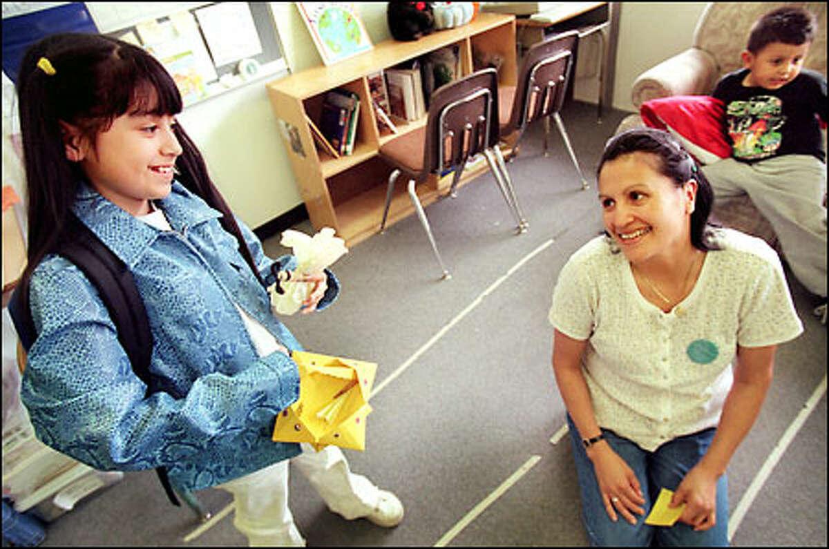 Ericka Alvarez, a third-grader at Cedar Valley Community School, shows her mother, Brenda Bob, crafts she made in class. Ericka gave her savings to help classmate Victor Leyba.