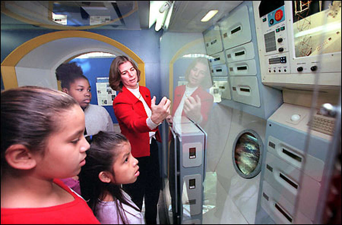 Astronaut Dr. Bonnie Dunbar explains the International Space Station exhibit to Seahurst Elementary School Students at the Museum of Flight yesterday, National Space Day. The new exhibit opens today and runs through Nov. 30. Listening in are, from near to far, Candy Olive (in red top), Mildred Alverez and Ollian Taylor, Dunbar, who grew up near Sunnyside, has logged more than 1,200 hours in space.