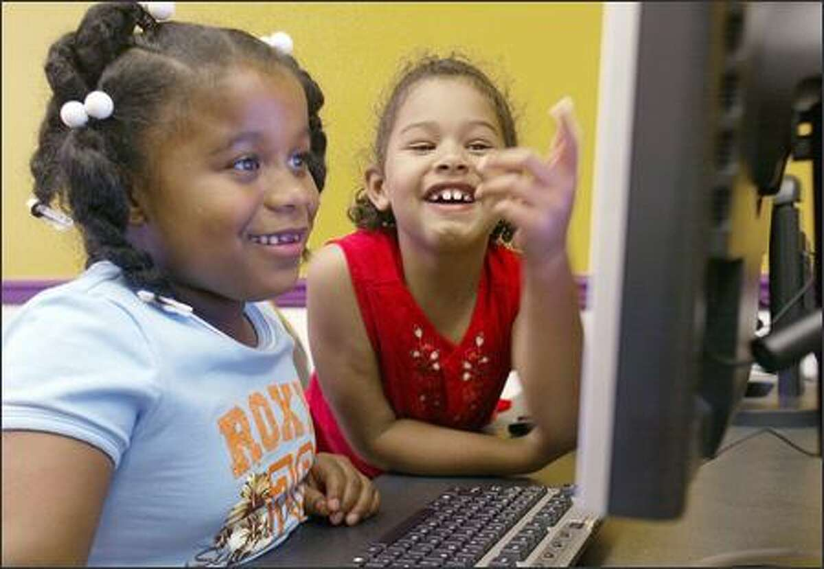 TechStart students Yazmine Mobley, 6, and Elise Dziko, also 6, help each other on the computers during a computer lab.