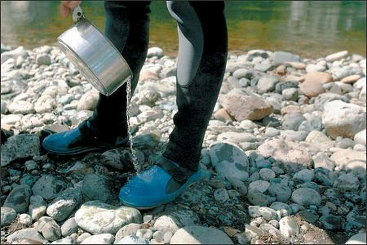 Paul Schutte warms his feet with leftover cooking water before the group continues its trip.