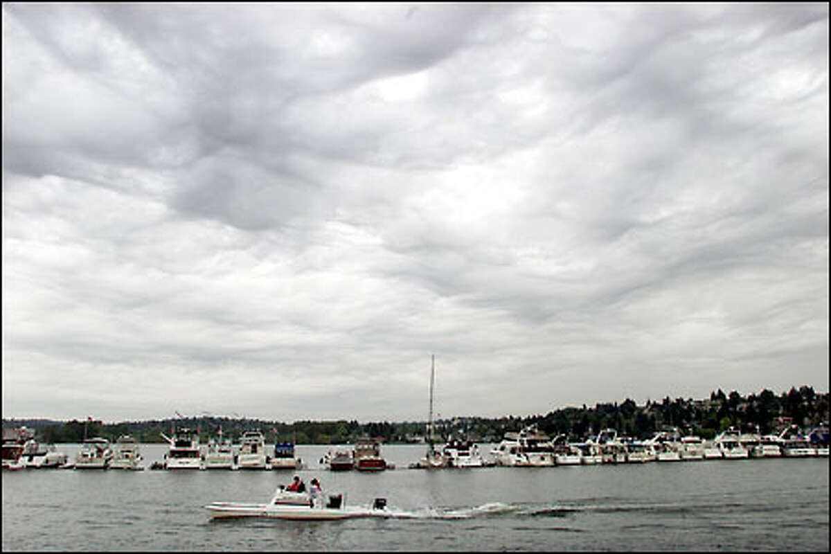 Boats tie up along a log boom on Lake Washington, waiting for the Opening Day of boating season today. Yesterday's ominous clouds were expected to give way to scattered showers today, becoming partly sunny by the afternoon. About 30 boating organizations are participating in the events, and hundreds of people are expected to watch from at least 1,000 boats moored on the water.