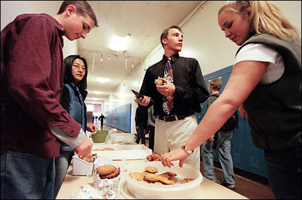 Ben Roseth, left, and Jody Hanson sell baked goods in the hallway at Garfield High School during lunch period yesterday to raise money for a sprinkler system for a restroom. Taking advantage of the sale at right are David Eaton and Jewel Benveniste-Campbell.