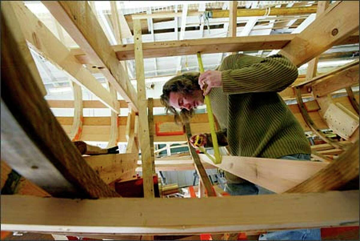 Michael Fenter measures the deck position as he establishes the location of floor boards in a 24-foot motor launch the students are building at the Northwest School of Wooden Boatbuilding.