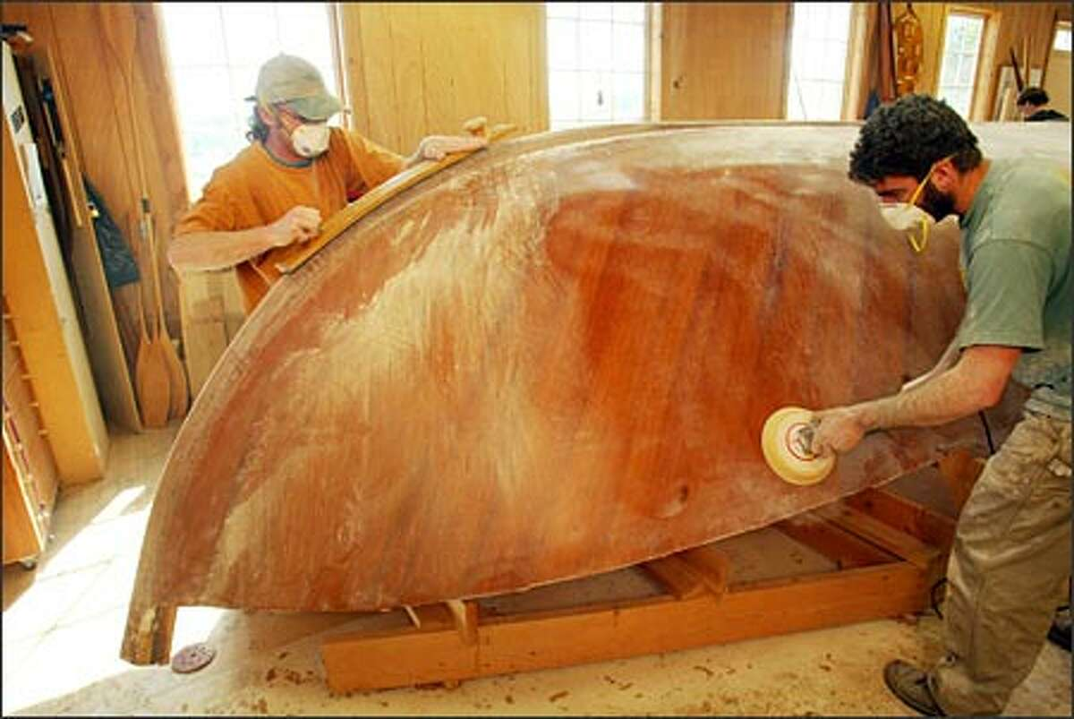 Andrew Greenwalt, left, and Lee Beers sand a 23-foot Gartside skiff built with mahogany planks.