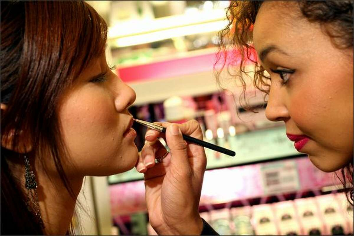 Sang Cao, left, from Seattle has lipstick applied by Too Faced makeup artist Mercedes Craft on Tuesday at Sephora in Seattle.