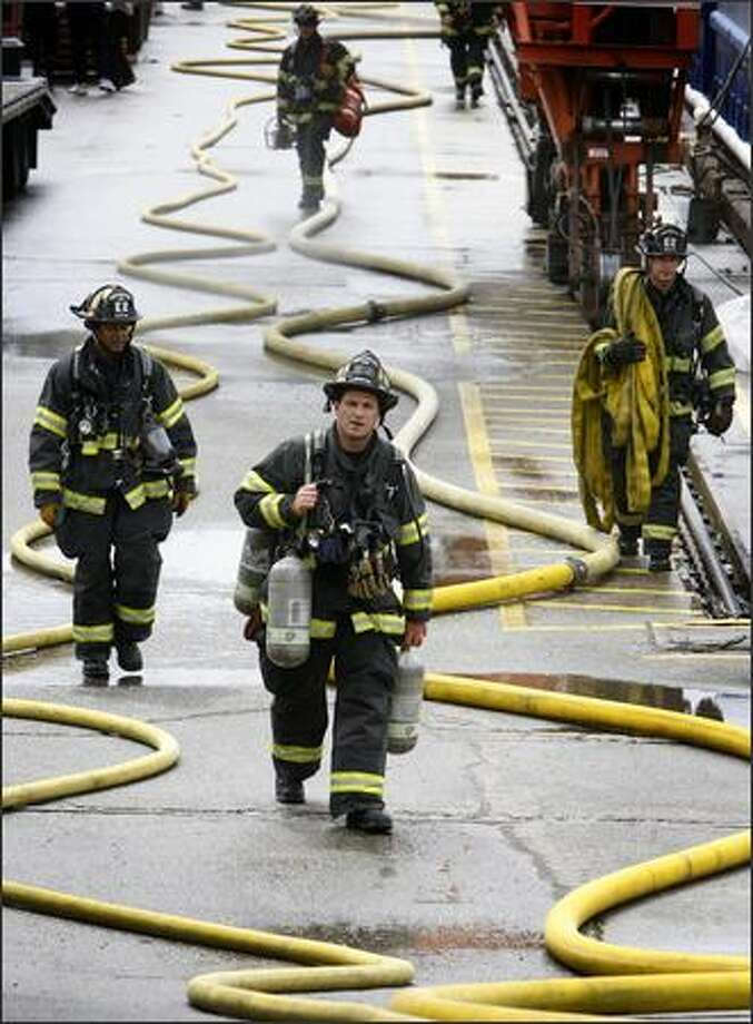Seattle Firefighters walk back to their trucks after a fire was extinguished on a boat in drydock on Tuesday on North Northlake Way and Densmore Avenue North on Lake Union. The fire was quickly extinguished but because fires on boats have potential to escalate quickly and are difficult to fight the response to the two-alarm fire was significant with about 100 firefighters including the marine rescue team. The firefighters had difficulty early in fighting the fire when a nearby hydrant malfunctioned. Photo: Joshua Trujillo, Seattlepi.com / seattlepi.com