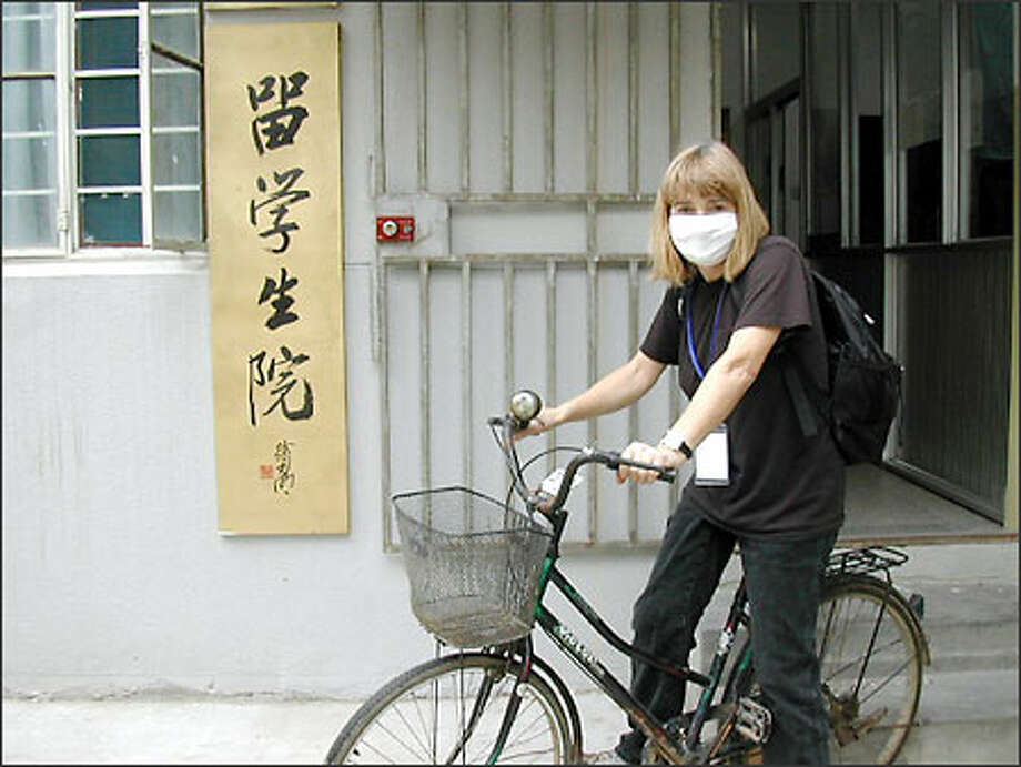 Michele Van Slyke lives at the last door before the guarded back gate of the arts institute campus. The SARS protection mask also serves to filter the air from the dust created by Nanjing's traffic.(Courtesy of Michelle Van Slyke)