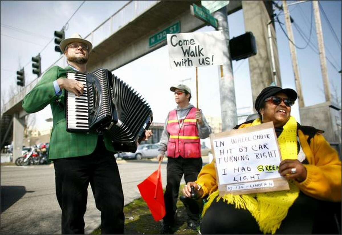 Brandy Sebron-Kelley, right, holds up a sign which details how she was hit by a car at North 130th Street and Linden Avenue North while in a crosswalk and in her wheelchair. Sebron-Kelley was joined by Steve Rice, playing the accordion, and others during a protest by residents of nearby senior communities at North 130th Street and Aurora Avenue North.