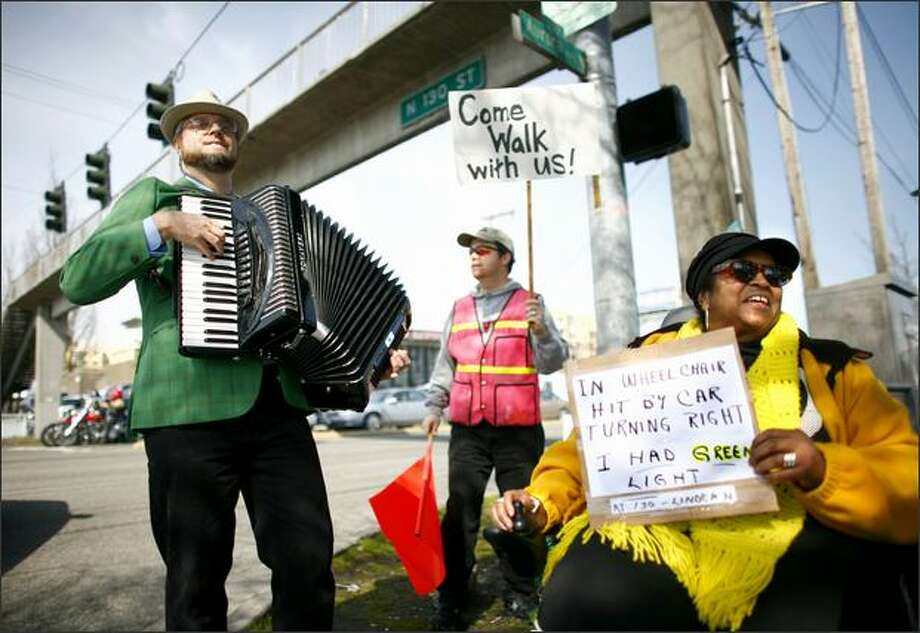 Brandy Sebron-Kelley, right, holds up a sign which details how she was hit by a car at North 130th Street and Linden Avenue North while in a crosswalk and in her wheelchair. Sebron-Kelley was joined by Steve Rice, playing the accordion, and others during a protest by residents of nearby senior communities at North 130th Street and Aurora Avenue North. Photo: Joshua Trujillo, Seattlepi.com / seattlepi.com