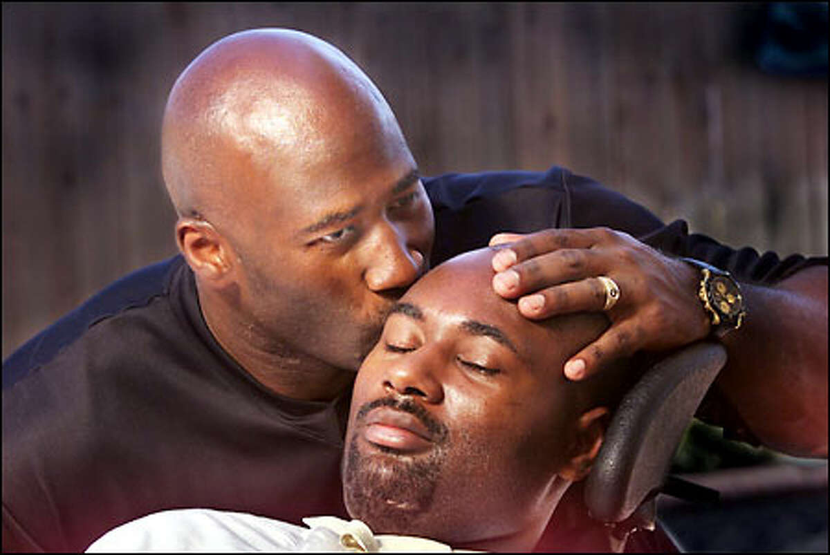 Last summer at his home in Fresno, Calif., David Williams kisses his brother Curtis, a quadriplegic since he was injured in a Husky football game.