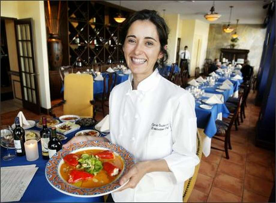 Executive chef Clara Gutierrez at Seattle's Madrid 522, holds a plate of Spanish piquillo peppers, stuffed with shrimp and arugula. Photo: Scott Eklund, Seattle Post-Intelligencer / Seattle Post-Intelligencer