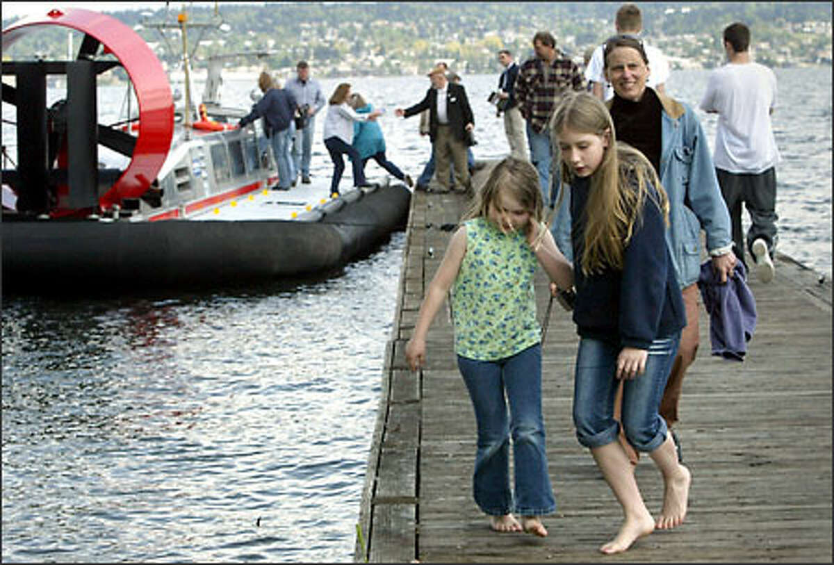 Erin Metteer, left, 7, and her sister, Alec, 12, walk off the dock at the Sand Point Magnuson Park boat launch yesterday after taking a ride on a new Griffon Hovercraft built by Kvichak Marine Industries Inc.