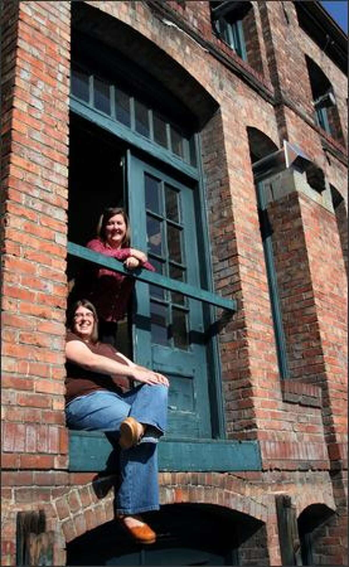 Sacha Davis, sitting, and Kathy Nyland are pictured at the Rainier Ice and Cold Storage Building, which contains artist studios and is considered a Georgetown landmark.