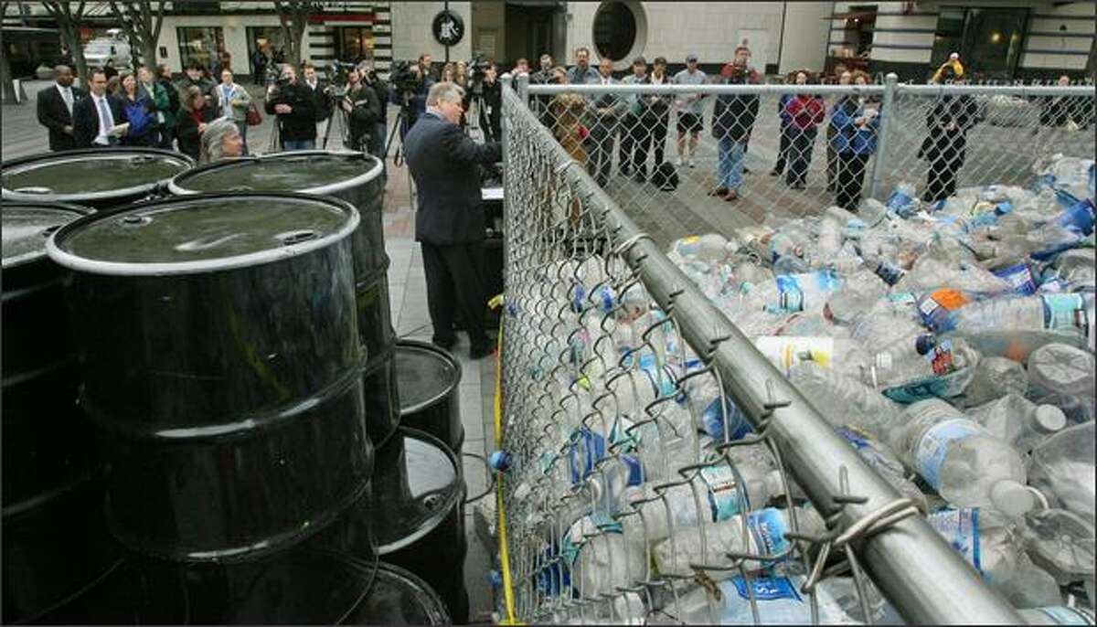 Mayor Greg Nickels speaks to the news media at Westlake Park on Wednesday about his campaign to promote Seattle's drinking water. On hand were 56 barrels representing the oil needed to produce and transport the number of plastic bottles discarded by Seattle residents in a 12-hour period.
