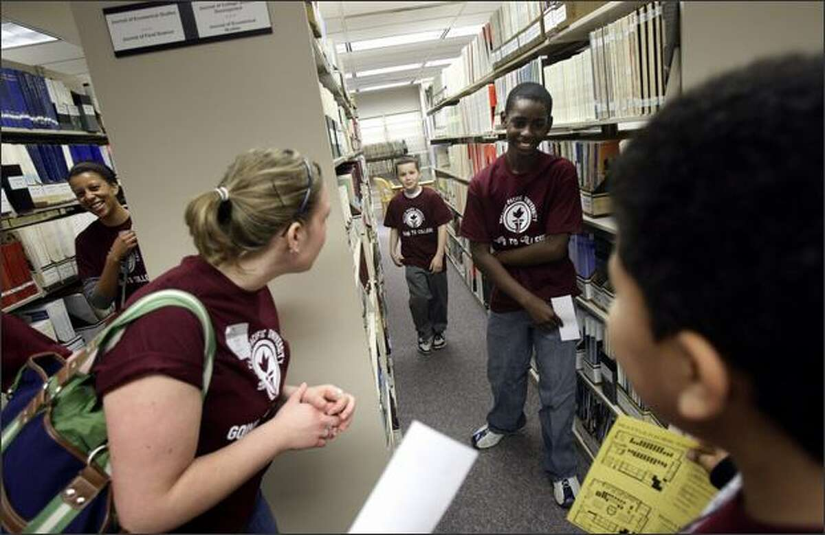 Zion Preparatory Academy fifth-graders Anthony Childs, center; Ethan Rhone, second right; and Giaunie Hendrix, right, walk through the stacks as Seattle Pacific University chaperones Teylar Greer, left, and Whitney Bigger watch Wednesday during a