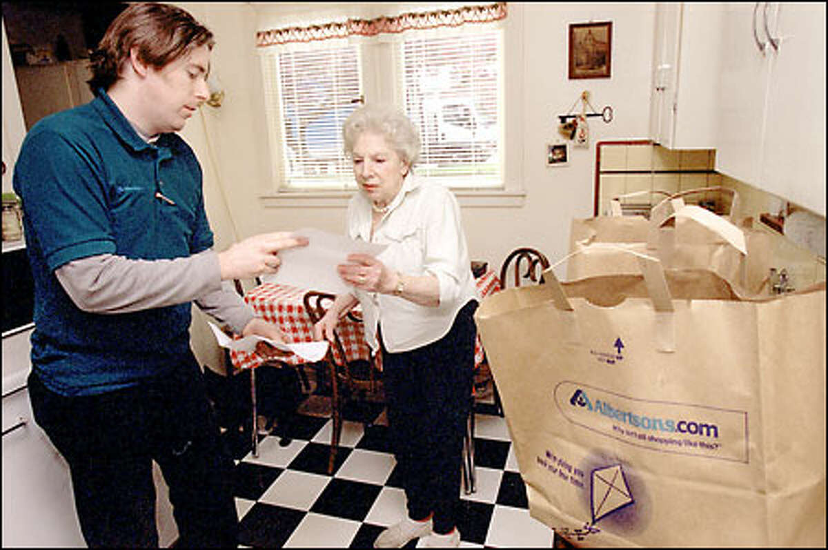 Mark Azimov goes over paperwork with Gertrude Racz after delivering groceries from Albertson's.