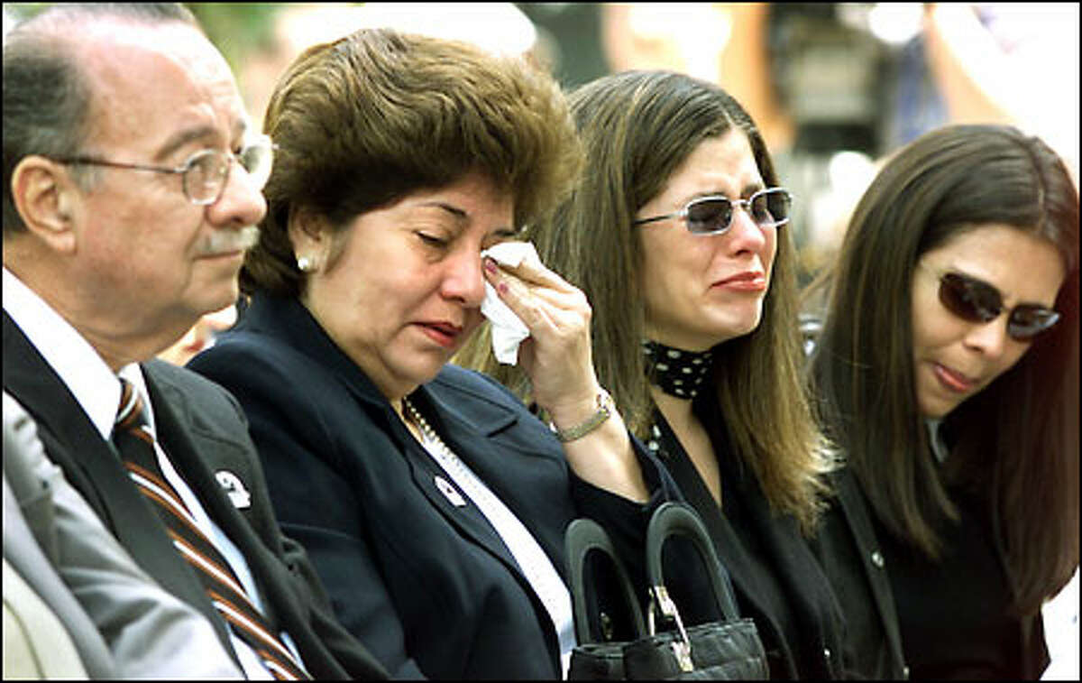 Rosathe Underwood, second from right, weeps during a memorial service for fallen law enforcement officers, held yesterday in downtown Seattle. Her husband, Des Moines police Officer Steven J. Underwood, was shot to death last year after stopping a car on Pacific Highway South. With her are her parents, Angel and Patricia Loor, left, and a friend, Ursula Rosien, right.