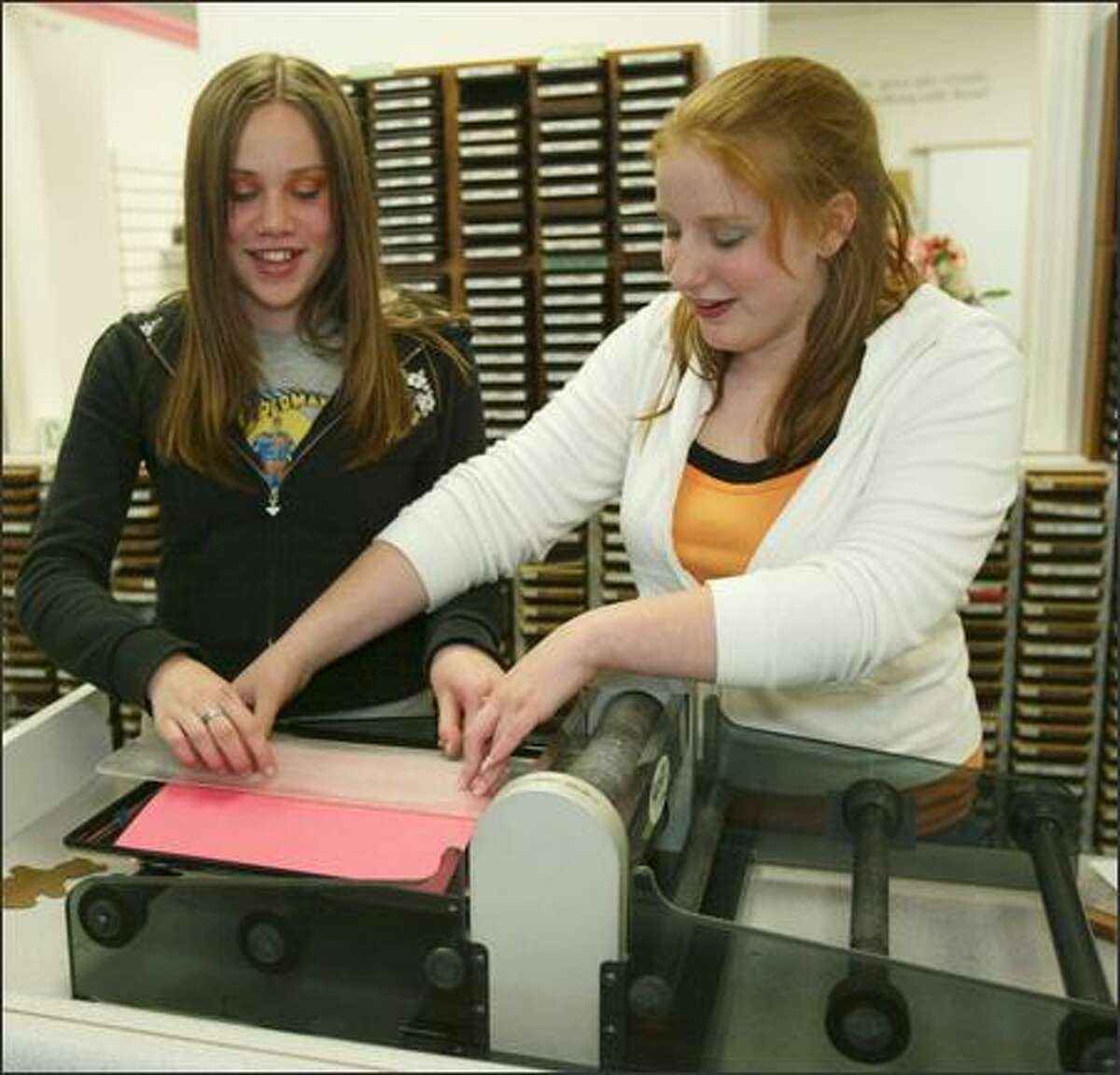 Cassandra Boseek, 13, left, and Kaila Sax, 13, use an expensive die cutter to cut out various shapes during a beginning scrapbooking class at Lasting Memories in Lynnwood.