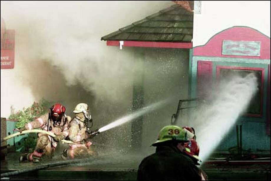 Firefighters hose down Mystical Mermaid, one of six businesses at First and Spring streets in Friday Harbor that completely burned down Thursday. Photo: Meryl Schenker, Seattle Post-Intelligencer / Seattle Post-Intelligencer