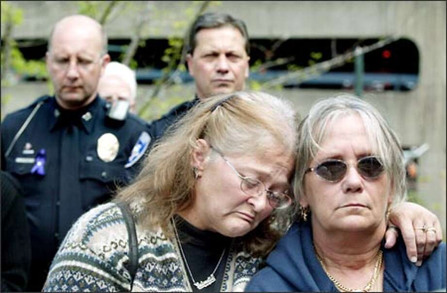 "Antoinette Bunch, left, and Nancy Bertucci, who said they are both victims of domestic violence, mourn at a memorial held for Crystal Brame Friday at Theatre Square Park in Tacoma. Hundreds gathered at the park, just down the block from the theater where a 14-year-old Crystal danced in ""The Nutcracker."" Yesterday was an official day of mourning in Tacoma. Photo: Dan DeLong, Seattle Post-Intelligencer / Seattle Post-Intelligencer"